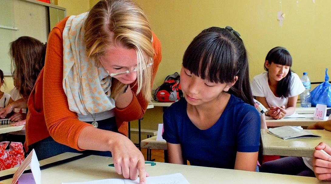 A Projects Abroad volunteer helps her student with her classwork at a teaching placement in Mongolia